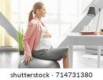 young pregnant woman working in ... | Shutterstock . vector #714731380