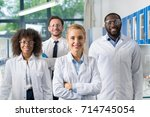 smiling group of scientists in... | Shutterstock . vector #714745054