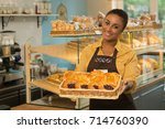cheerful african female baker... | Shutterstock . vector #714760390