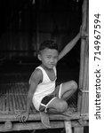 Small photo of Hulu Slim,Perak Malaysia - 13 September 2017 : : A boy of Semai Orang Asli sitting at the door a rattan house. Semai Orang Asli tribal live at Hulu Slim in Perak.