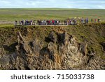 Small photo of Busloads of visitor on the right bank of Godafoss falls in high tourism season, on top of an interesting geological formation