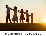 silhoutte of happy family... | Shutterstock . vector #715047616
