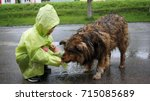 the child feeds a stray dog in... | Shutterstock . vector #715085689