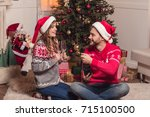 happy young couple in santa... | Shutterstock . vector #715100500