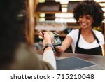 cashier accepting payment over...   Shutterstock . vector #715210048