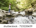 Stock photo girl next to the waterfall of the bucket in the selva de irati in navarra spain 715220659