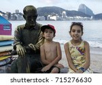 Small photo of RIO DE JANEIRO, BRAZIL - SEPTEMBER 7th, 2017: Tourist place in Copacabana Beach Orla. Children sitting with the Statue of the famous poet Carlos Drummond Andrade with Sugar Loaf Mountain on the back.
