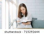 asian woman reading bible book... | Shutterstock . vector #715292644