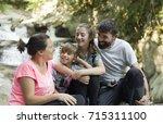 family sitting on some rocks... | Shutterstock . vector #715311100