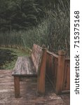Small photo of Old wooden bench on a wooden deck in overlooking a forest lake with lily pads and plant life in the background