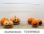 Stock photo halloween pumpkins with painted faces on a wooden table on a background of white boards halloween 715459810