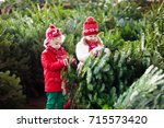 family selecting christmas tree.... | Shutterstock . vector #715573420