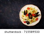 seafood fettuccine pasta with... | Shutterstock . vector #715589533