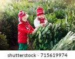 family selecting christmas tree.... | Shutterstock . vector #715619974