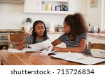 two sisters sitting at table in ... | Shutterstock . vector #715726834