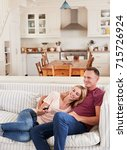 couple sitting on sofa watching ... | Shutterstock . vector #715726924