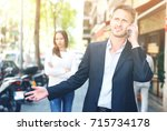 Small photo of Young man during serious telephone conversation on background of disappointed girl