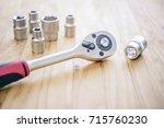 closeup block wrench on wooden... | Shutterstock . vector #715760230