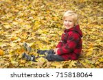 cute blond boy walks in autumn... | Shutterstock . vector #715818064