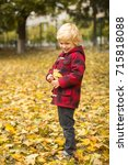 cute blond boy playing with... | Shutterstock . vector #715818088