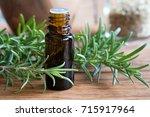 a dark bottle of rosemary... | Shutterstock . vector #715917964