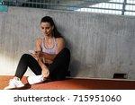 young female runner resting...   Shutterstock . vector #715951060