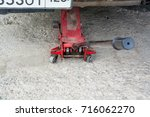 Small photo of Car lift up by jack stand ( axle stand ). Red jack stand ( axle stand ) in action.