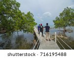 Small photo of KOTA TINGGI,MALAYSIA-SEPTEMBER 16 2017:A group of Malay teenagers walking on a alleviated concrete walk path on a beach