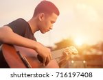 practicing in playing guitar.... | Shutterstock . vector #716197408