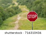 stop sign against green forest...