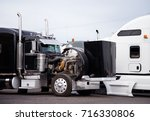 Small photo of Large black classic big rig semi truck with an open hood is on a technical inspection of the engine to prepare truck and make sure that everything works properly for the next commercial cargo delivery
