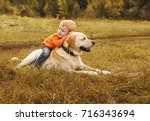Little Boy Sits Astride Dog On...
