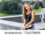 a young girl with a black t... | Shutterstock . vector #716378899