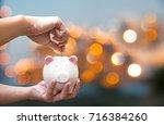 man holding piggy and putting a ...   Shutterstock . vector #716384260