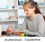 schoolgirl  repairing the... | Shutterstock . vector #716384944