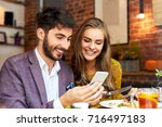 happy cute young couple looking ... | Shutterstock . vector #716497183