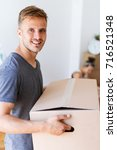 moving day. young man carrying... | Shutterstock . vector #716521348