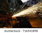 man sawing metal by grinder | Shutterstock . vector #716541898