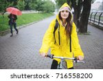 woman cycling in the rain   Shutterstock . vector #716558200