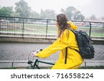 woman cycling in the raincoat.... | Shutterstock . vector #716558224