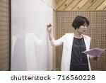businesswoman at whiteboard in... | Shutterstock . vector #716560228
