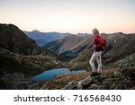 girl hiker standing on a brink... | Shutterstock . vector #716568430