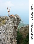 Small photo of Cheerful young woman sitting with dangling legs on steep cliff.