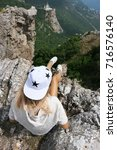Small photo of Reckless young woman sitting with dangling legs on high steep cliff. Back view.