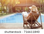 Small photo of relaxation concept, woman reading book near swimming pool of hotel