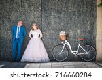 bride and groom with a bicycle... | Shutterstock . vector #716660284