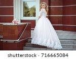 lovely young bride in wedding... | Shutterstock . vector #716665084