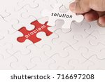 Small photo of Management concept with hand holding piece of jigsaw puzzle with problem and solution wording