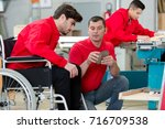 disabled worker in wheelchair... | Shutterstock . vector #716709538
