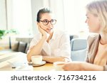 two friendly colleagues... | Shutterstock . vector #716734216